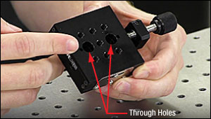 The oversized through holes in the top plate of a translation stage are used to access the mounting points in the base plate.